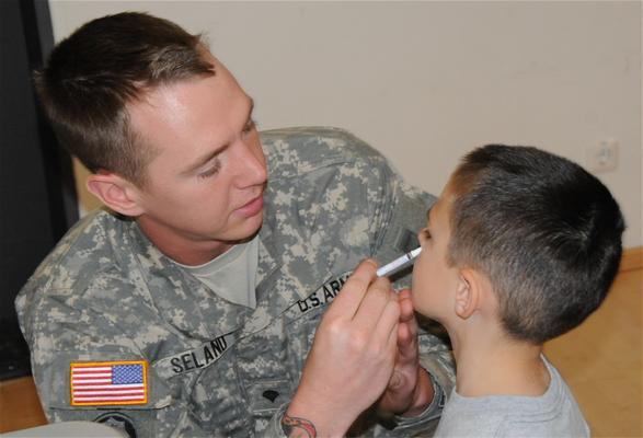 A Soldier provides a flu vaccine to a child